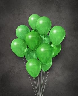 Grupa zielonych balonów powietrznych na ciemnym betonie