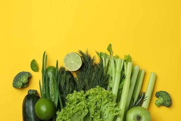 Grupa zielonych warzyw na żółtym tle