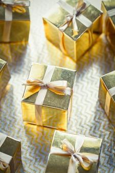 Grupa złotych błyszczących pudeł prezentowych, piękne złote opakowanie zaskakuje kokardą na błyszczącym tle