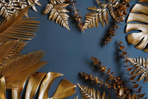 Grupa złotych liści na ciemnym czarnym tle monstela liście kokosowe liście bananowca paproć