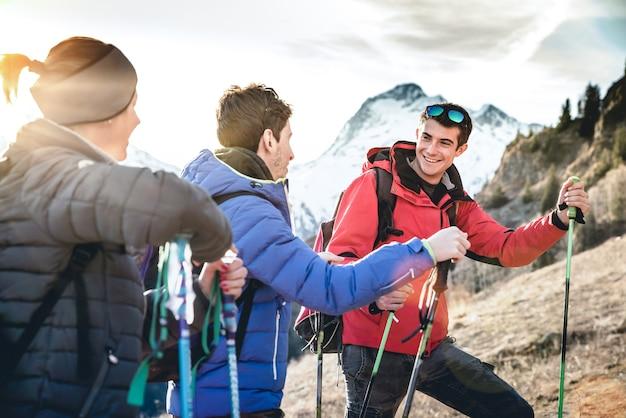 Grupa znajomych na trekkingu na francuskich alpach o zachodzie słońca - skup się na właściwym facecie