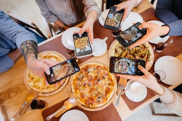 Grupa znajomych robi zdjęcie z bliska pysznej pizzy dla blogowej pizzerii