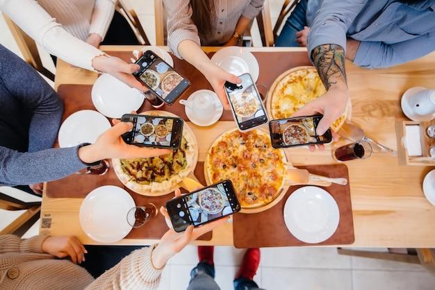 Grupa znajomych robi zdjęcie z bliska pysznej pizzy na bloga, pizzerię