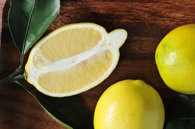 Grupa żółte cytryny z liśćmi na drewnianym talerzu