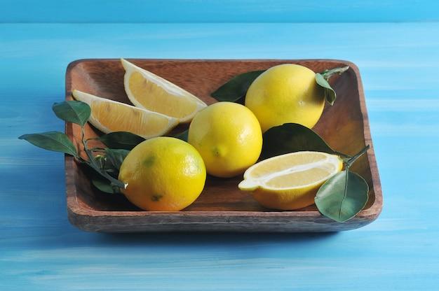 Grupa żółte cytryny z liśćmi na kwadratowym drewnianym talerzu