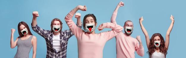 Grupa zwycięskich, szczęśliwych ludzi, kobiet i mężczyzn noszących maskę ochronną na niebieskim tle. modele wielorasowe. kolaż. pojęcie ludzkich emocji, wyraz twarzy, bezpieczeństwo, ochrona.