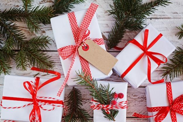 Grupowe białe pudełka na prezenty z czerwonymi wstążkami na stole. widok z góry