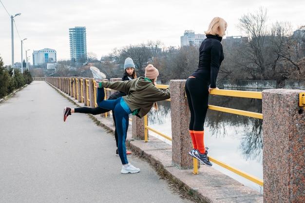 Grupowe zajęcia fitness na świeżym powietrzu. zorganizowane zajęcia gimnastyczne w parkach publicznych. trzy kobiety trenują razem w publicznym parku. pojęcie zdrowia, odnowy biologicznej i społeczności.