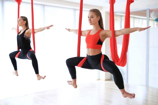 Grupowe zajęcia jogi przez powieszenie na czerwonej pościeli
