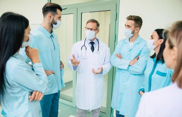 Grupowe zdjęcie młodych medyków podczas rozmowy ze starszym pewnym siebie lekarzem na korytarzu szpitalnym