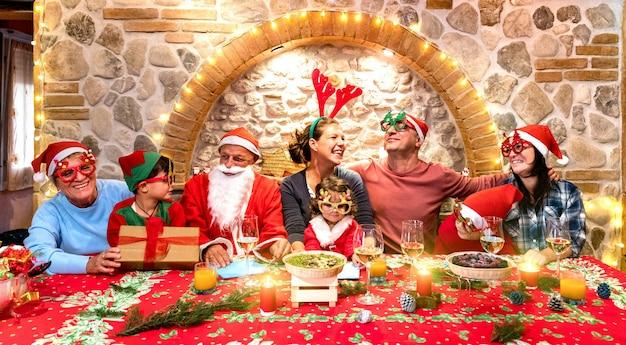 Grupowe zdjęcie szczęśliwej rodziny z czapkami świętego mikołaja, zabawy na świątecznym przyjęciu domowym