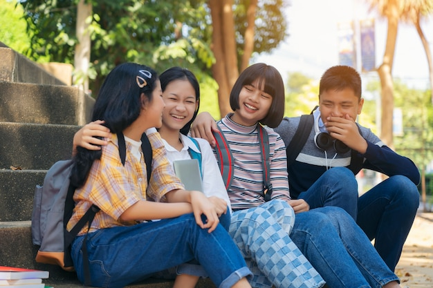 Grupowi studenccy młodzi ludzie i edukaci czytelnicza książka w miasto parku