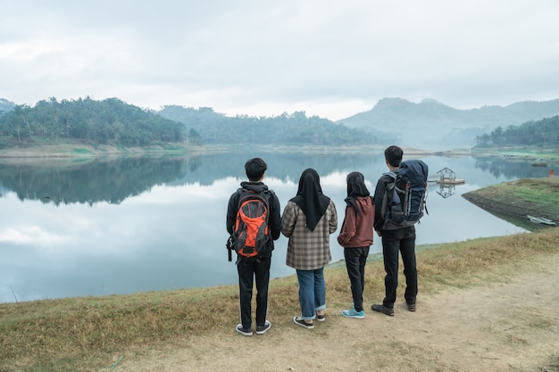 Grupowi wycieczkowicze z plecakami cieszy się widok na jezioro