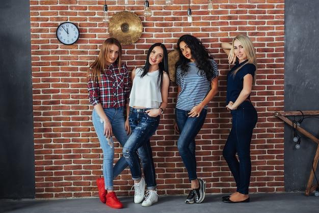 Grupowy portret najlepszych przyjaciółek z kolorowymi modnymi ubraniami trzymających przyjaciela pozujących na ścianie z cegły, ludzie w stylu miejskim bawią się, o stylu życia młodzieży