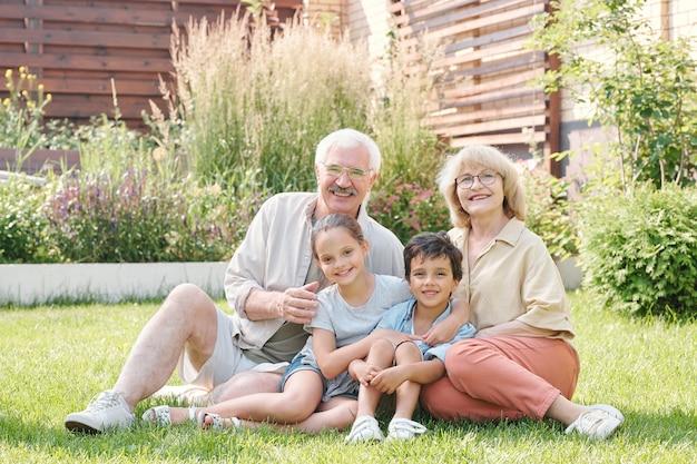 Grupowy portret wesołej babci, dziadka i dwójki wnuków siedzących razem na trawniku na podwórku