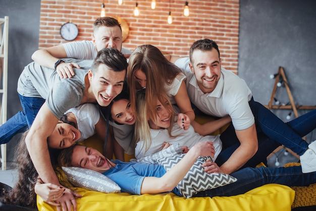 Grupowy portret wieloetnicznych chłopców i dziewcząt w kolorowych modnych ubraniach trzymających przyjaciela pozujących na ścianie z cegły, ludzie w stylu miejskim bawią się, o stylu życia młodzieży