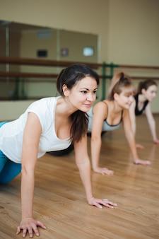 Grupuj kobiety na podłodze w siłowni robi pompki. klub sportowy