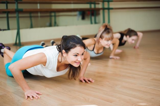 Grupuj kobiety na podłodze w siłowni robi pompki.