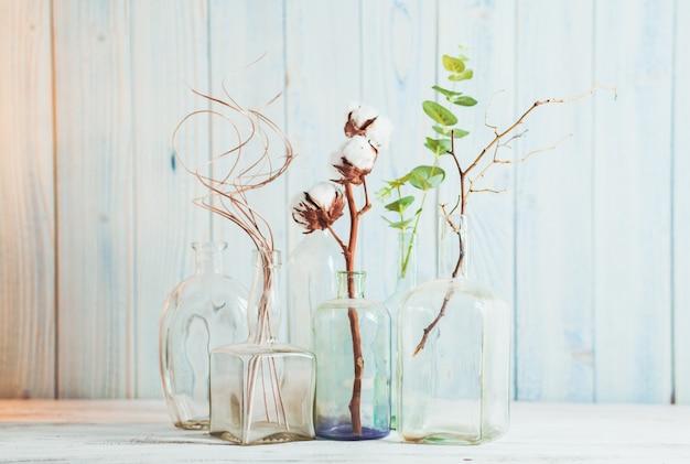 Grupuj ozdobne gałęzie w szklanych butelkach na drewnianym tle