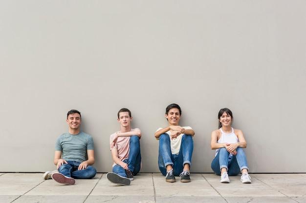 Grupuje młodych przyjaciół ono uśmiecha się wpólnie