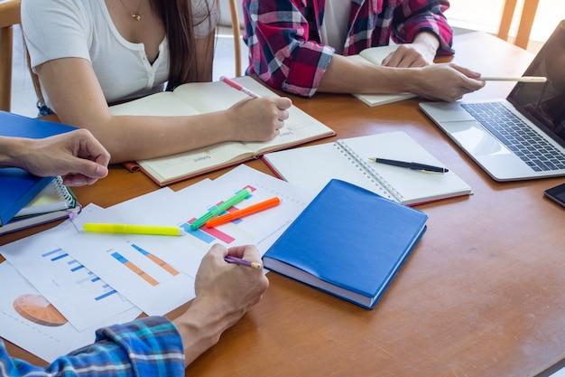Grupy studentów przeglądają informacje w książkach i laptopach