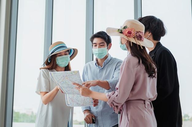 Grupy turystów noszą maski i oglądają mapy na lotnisku przed podróżą.