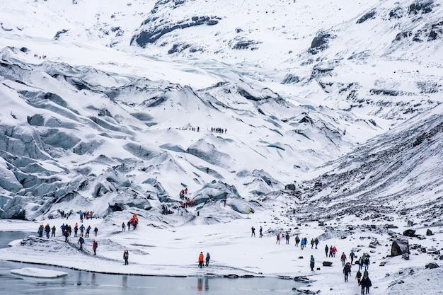 Grupy turystów pieszych wędrujących po śnieżnych, białych, surowych górach