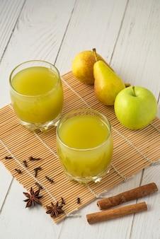 Gruszka i sok w szklanych kubkach na drewnianym stole