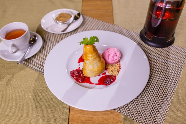 Gruszka w syropie i lody waniliowe na białym talerzu