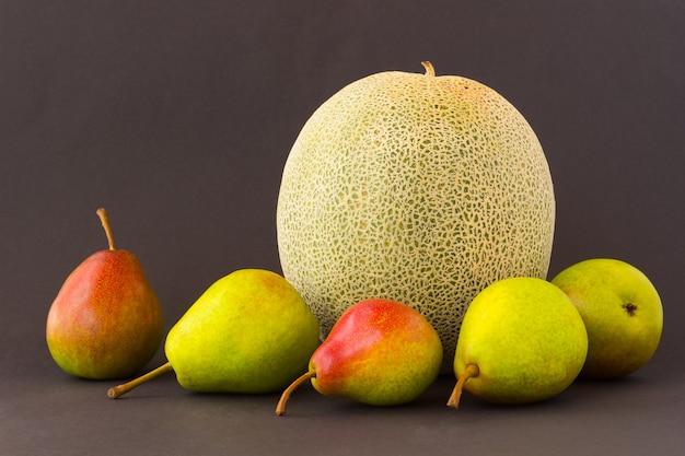 Gruszki i melon na czarnym stole