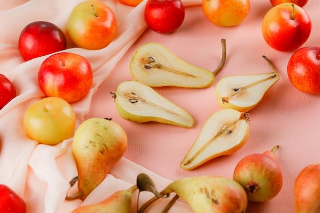 Gruszki i śliwki wysoki kąt widzenia na różowej i tekstylnej powierzchni