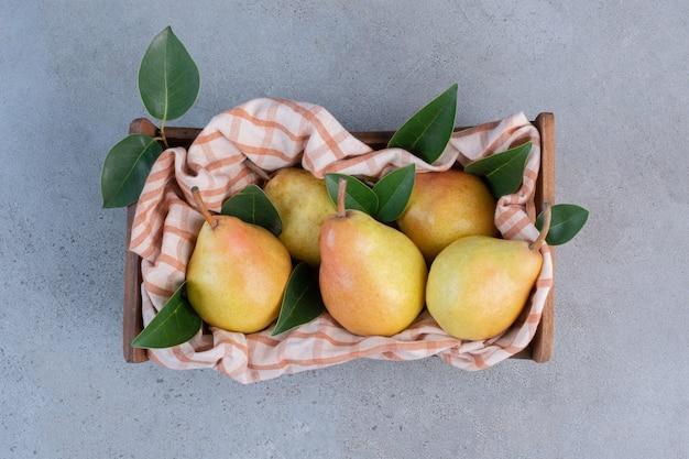 Gruszki, liście i ręcznik w drewnianym koszu na tle marmuru.