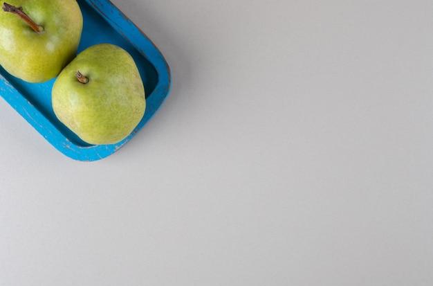 Gruszki na niebieskim talerzu na marmurze