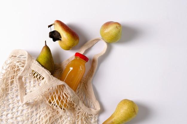 Gruszki odmiany pstrąg i konferencja z eko-sumką, małą na białym tle. w eko-supie znajduje się szklana butelka z sokiem owocowym. kopiowanie przestrzeni, układ płaski