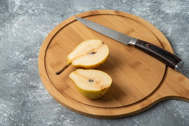 Gruszki pokrojone na pół na drewnianym talerzu.