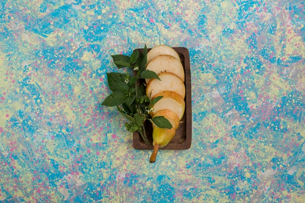 Gruszki pokrojone w plastry podawane z liśćmi mięty na drewnianym talerzu na środku