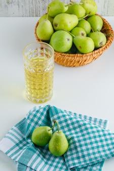 Gruszki w koszu z napojem, ręcznik kuchenny wysoki kąt na białym stole