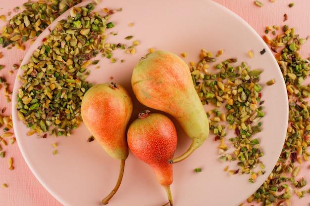 Gruszki w talerzu z ciętą pistacją