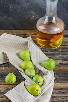 Gruszki z napojem cydrowym na ręczniku kuchennym na ścianie drewnianej i nieczysty