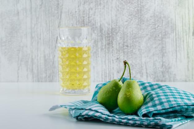 Gruszki z napojem, ręcznik kuchenny na białej i nieczysty ścianie