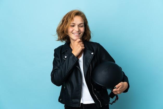 Gruzińska dziewczyna trzyma kask motocyklowy na białym tle na niebieskim tle, patrząc w bok i uśmiechając się