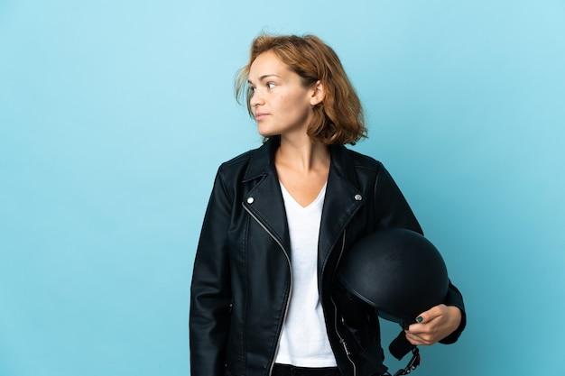 Gruzińska dziewczyna trzyma kask motocyklowy na białym tle na niebieskim tle patrząc w bok