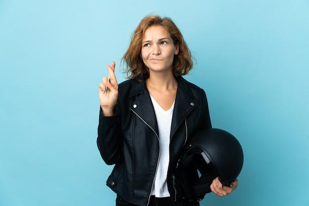 Gruzińska dziewczyna trzyma kask motocyklowy na białym tle na niebieskim tle z palcami skrzyżowanymi i życząc jak najlepiej