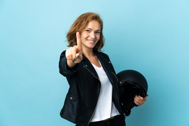 Gruzińska dziewczyna trzymająca kask motocyklowy na białym tle na niebieskim tle pokazująca i unosząca palec