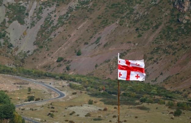 Gruzińska flaga macha przeciw dolinie stepantsminda, gruzja