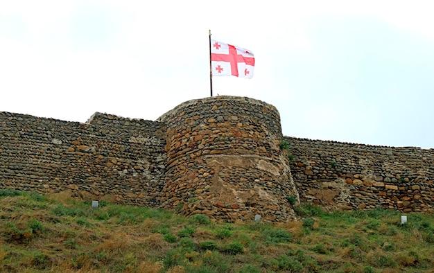 Gruzińska flaga machająca na średniowiecznej twierdzy gori, miasto gori, georgia