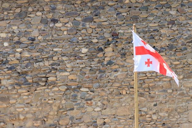 Gruzińska flaga na tle starego muru twierdzy