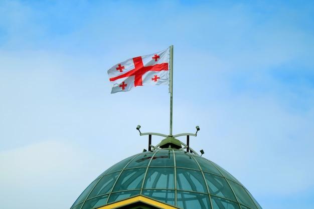 Gruzińska flaga narodowa lub flaga pięciu krzyży macha na niebieskim niebie