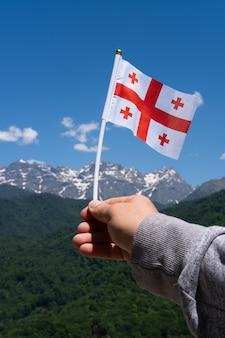 Gruzińska flaga w ręku człowieka na tle gór i błękitnego nieba