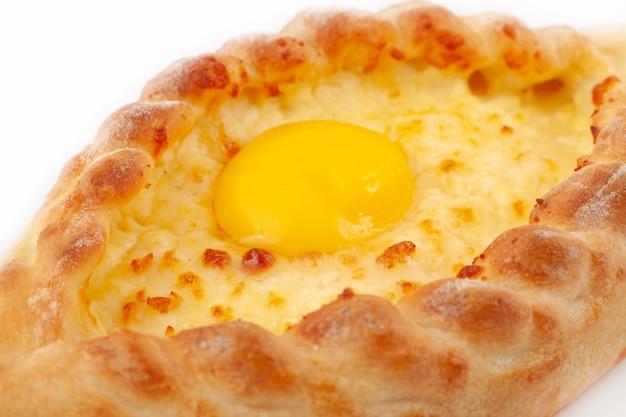 Gruziński chaczapuri krajowe ciasto z jajkiem, serem i masłem na talerzu na białym.